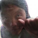 Tibetansk kvinna som vill ha en slant